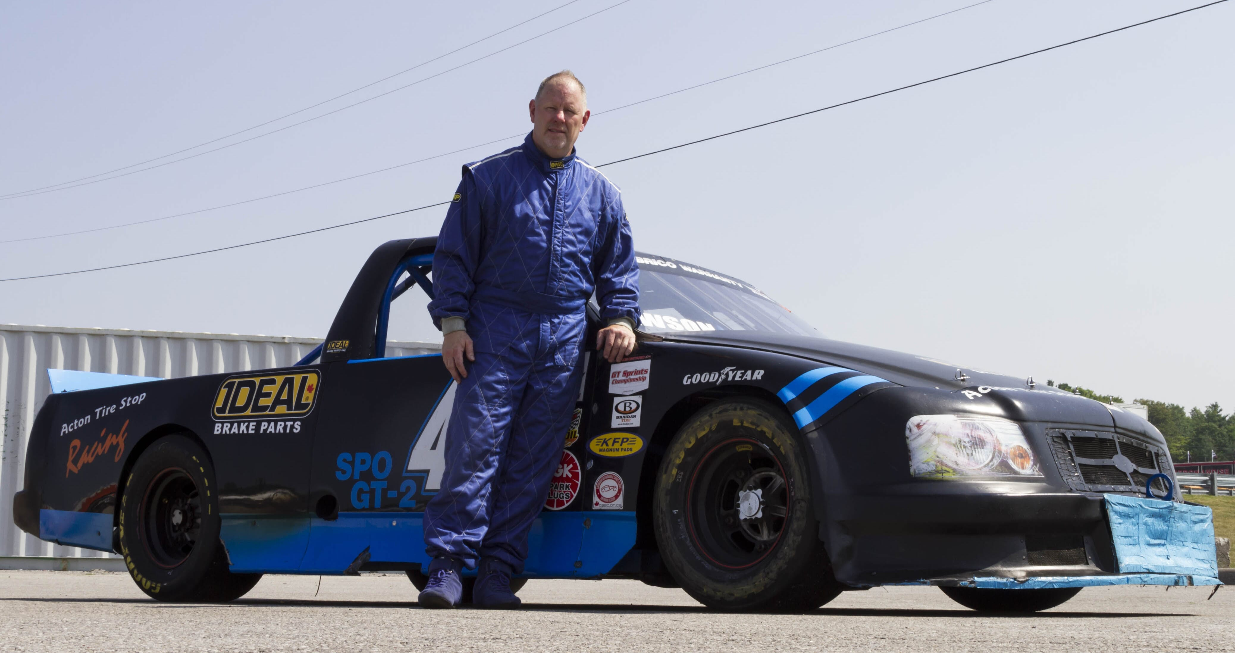 Chris standing with his custom F-150 looking for the checkered flag.