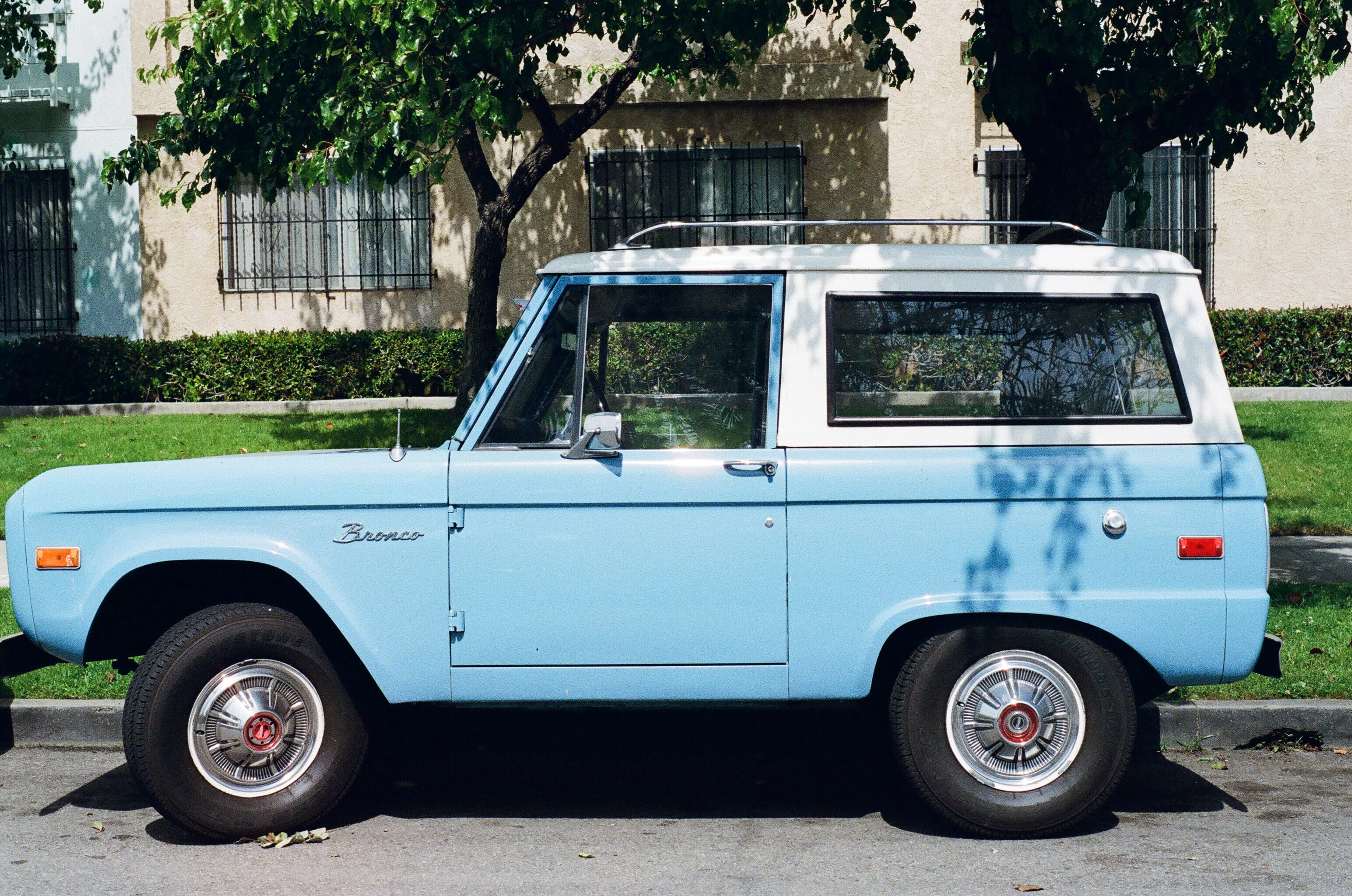 Vintage baby blue Ford Bronco parked on a the street side